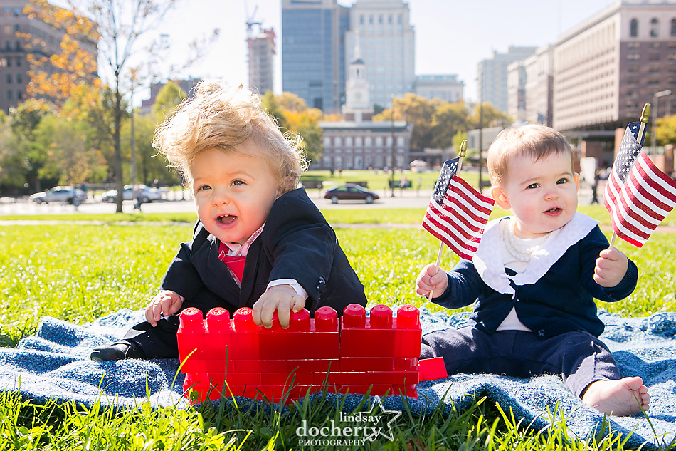 Baby Clinton and Trump in front of Independence Hall with blocks and flags