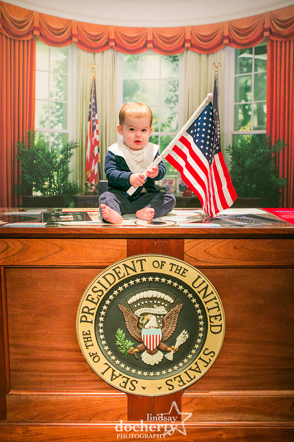 Baby Hillary Clinton in the Oval Office with a flag