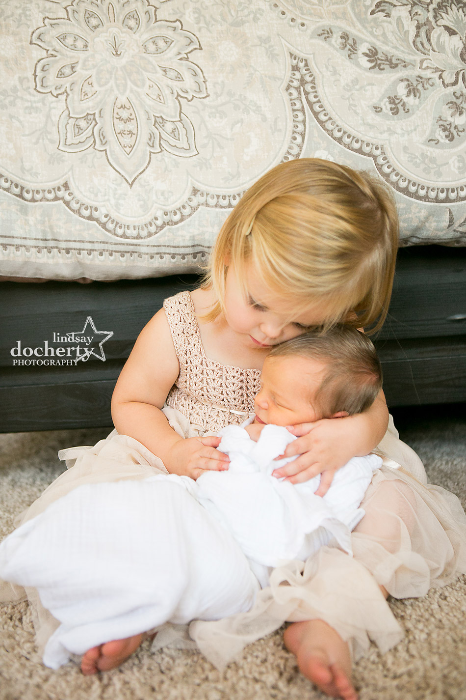 Big sister holding newborn baby brother for photo session in Philadelphia