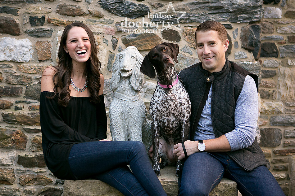 laughing engagement picture with dog statue at Ridley Creek State Park