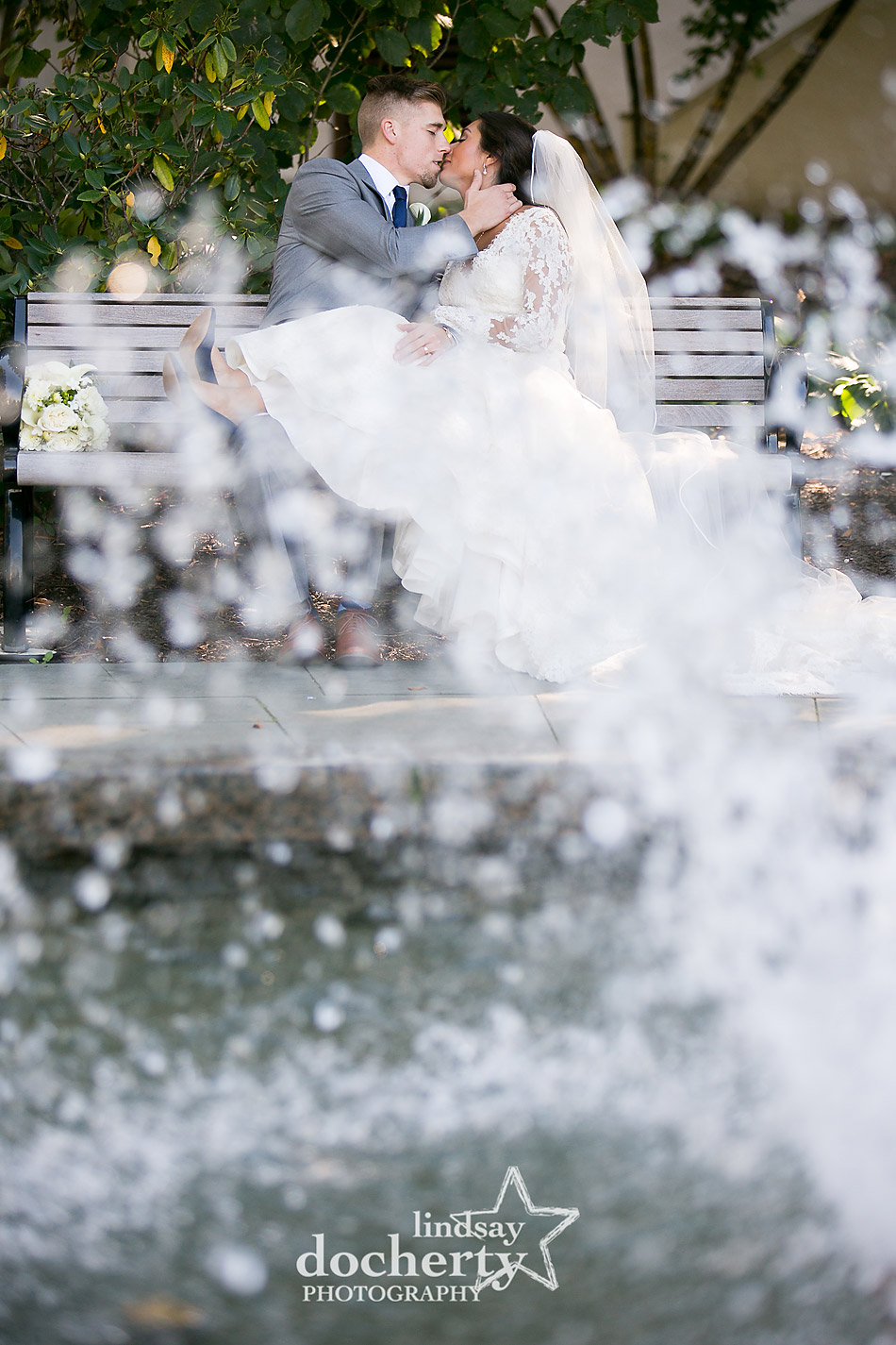 wedding day bride and groom kiss at fountain outside at Villanova University