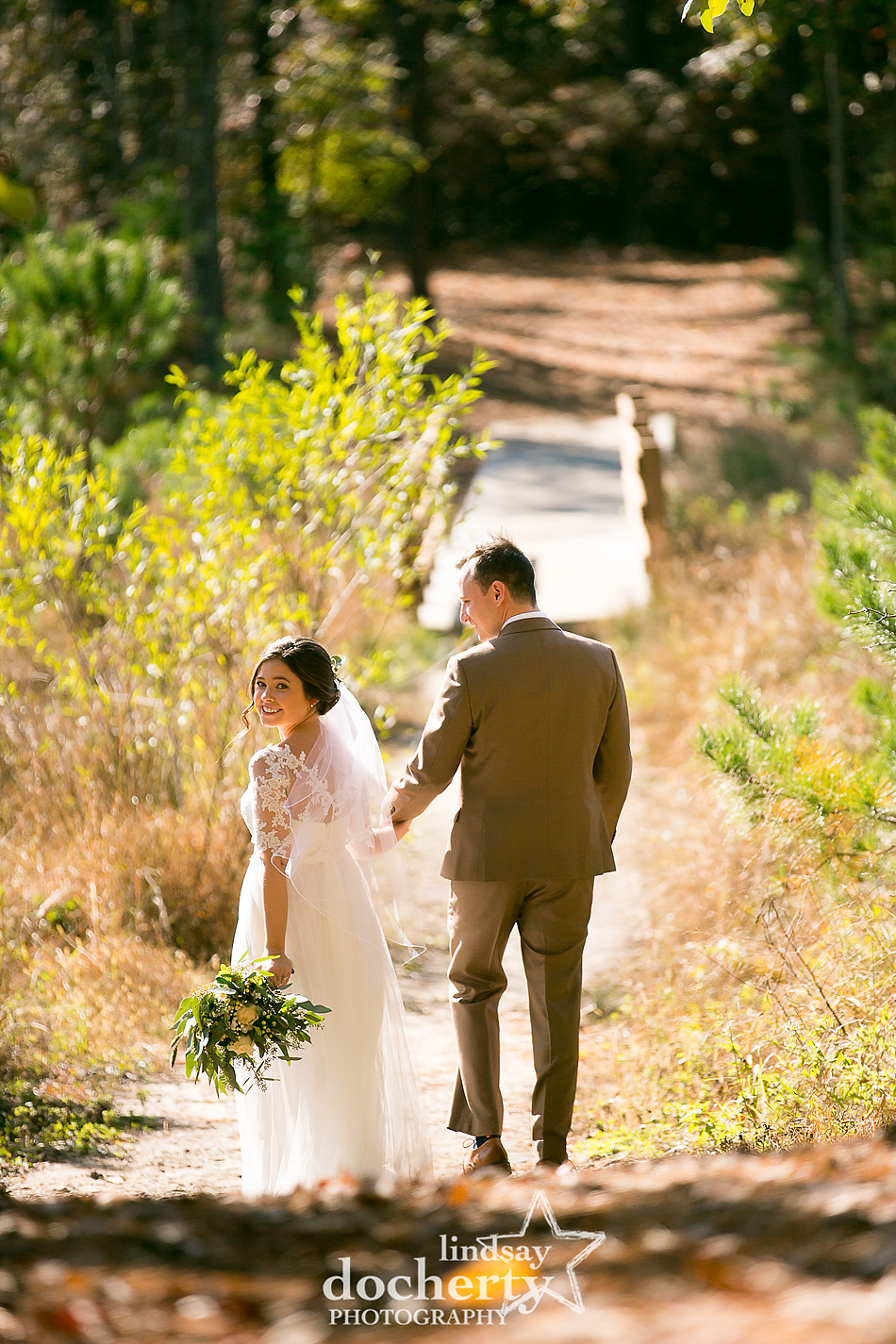 bride-and-groom-walk-down-path-at-camp-ockanickon-in-new-jersey