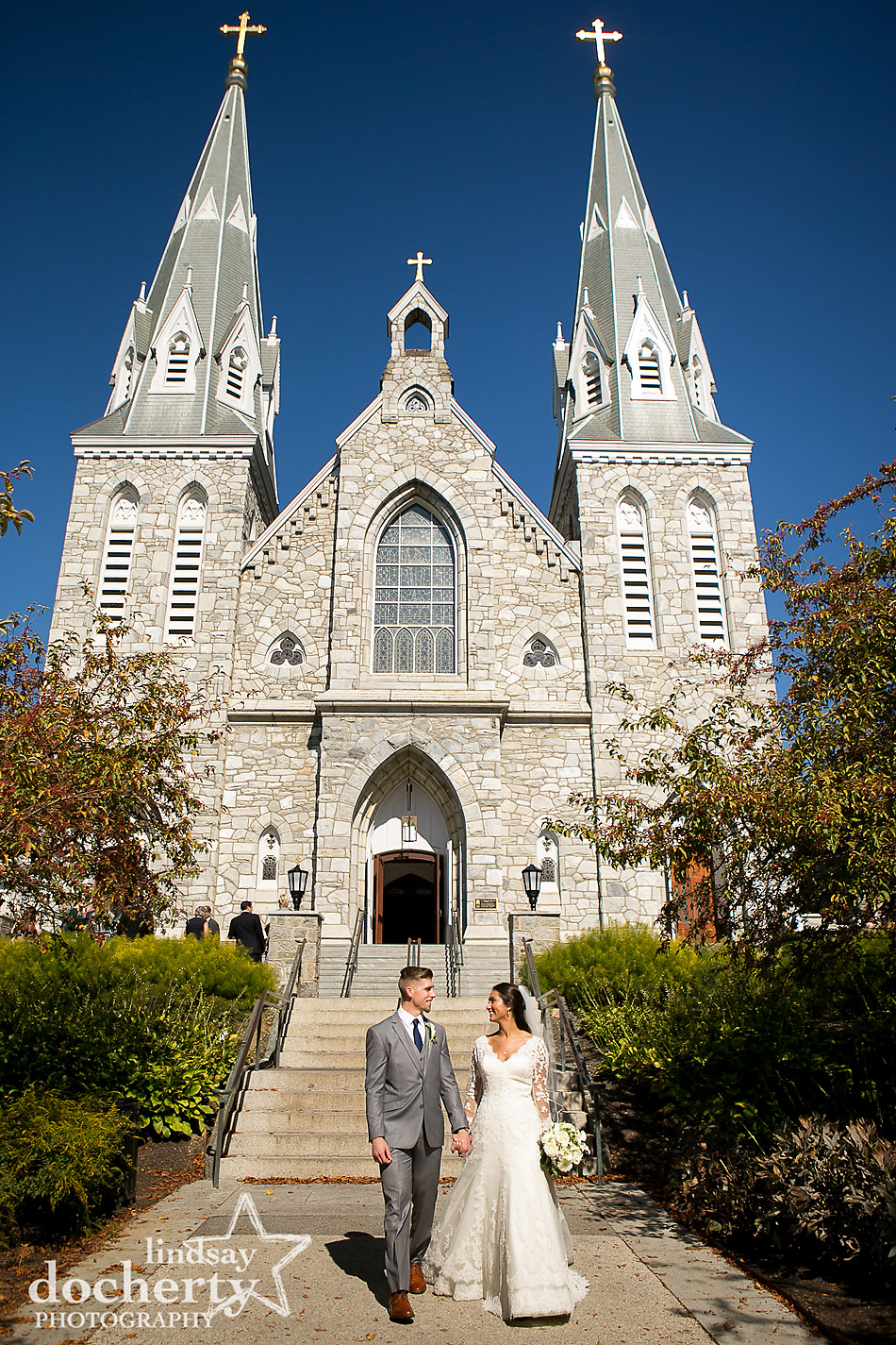 bride and groom walking along path outside after ceremony at Villanova University cathedral