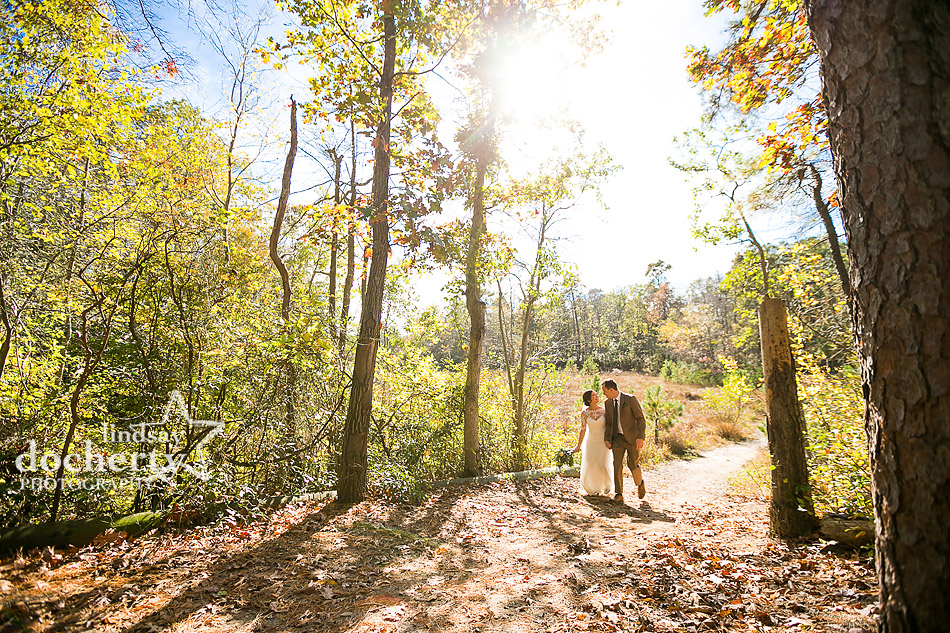 bride-and-groom-walking-through-woods-at-camp-ockanickon-wedding-in-new-jersey