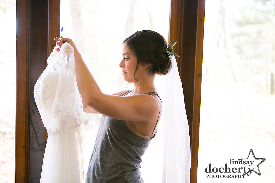 bride-holding-wedding-dress-before-ceremony-at-camp-ockanickon-in-new-jersey