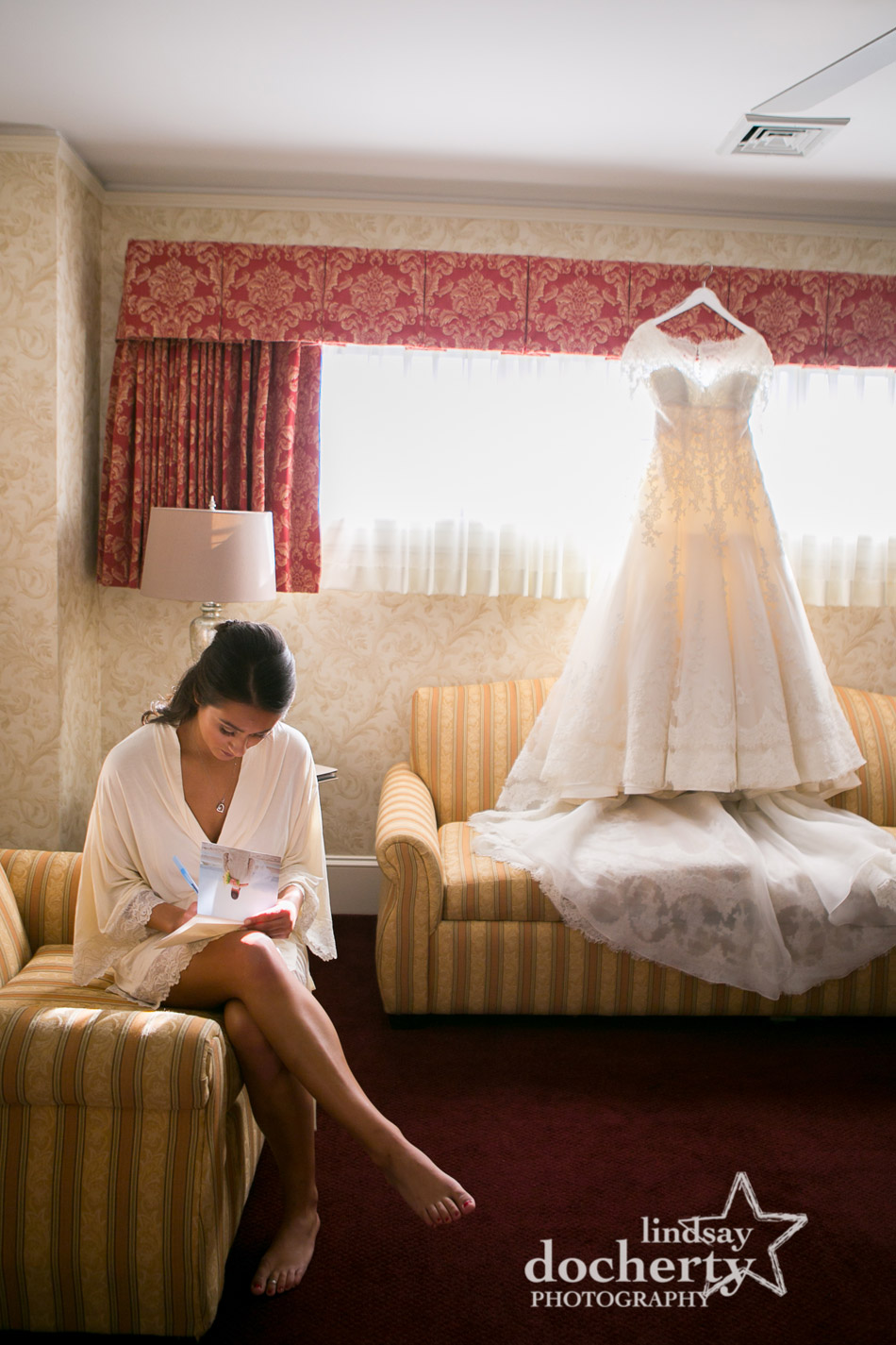 bride writing a letter to groom on wedding day in Wayne Hotel with dress