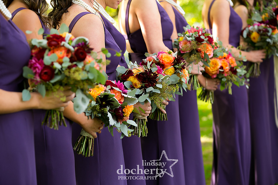 bridesmaids holding fall flowers in purple wedding dresses and pearls