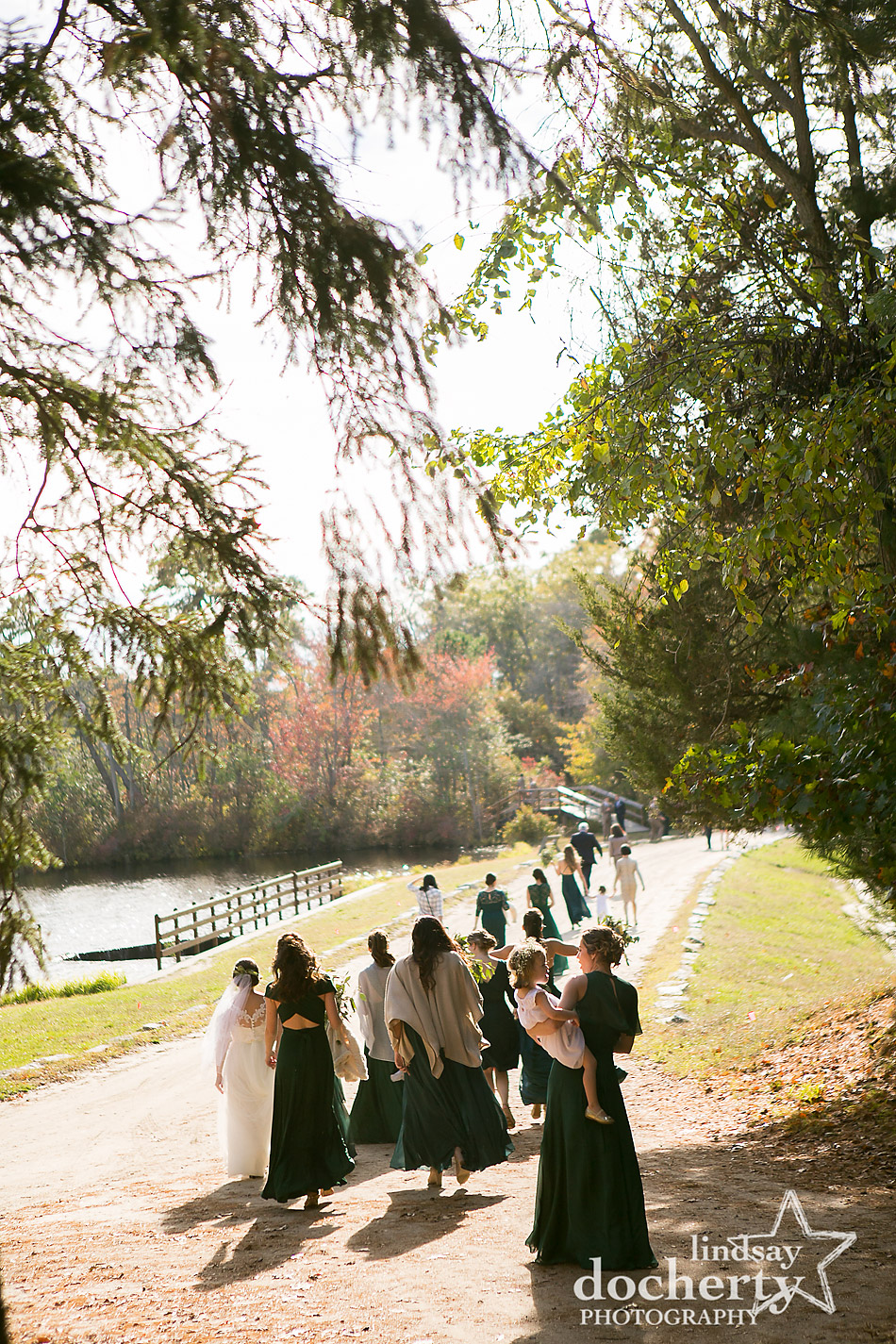 bridesmaids-walking-to-wedding-ceremony-at-camp-ockanickon-in-new-jersey
