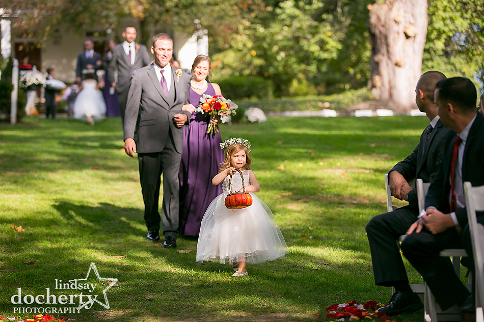 flowergirl tossing petals at outside ceremony at Riverdale Manor