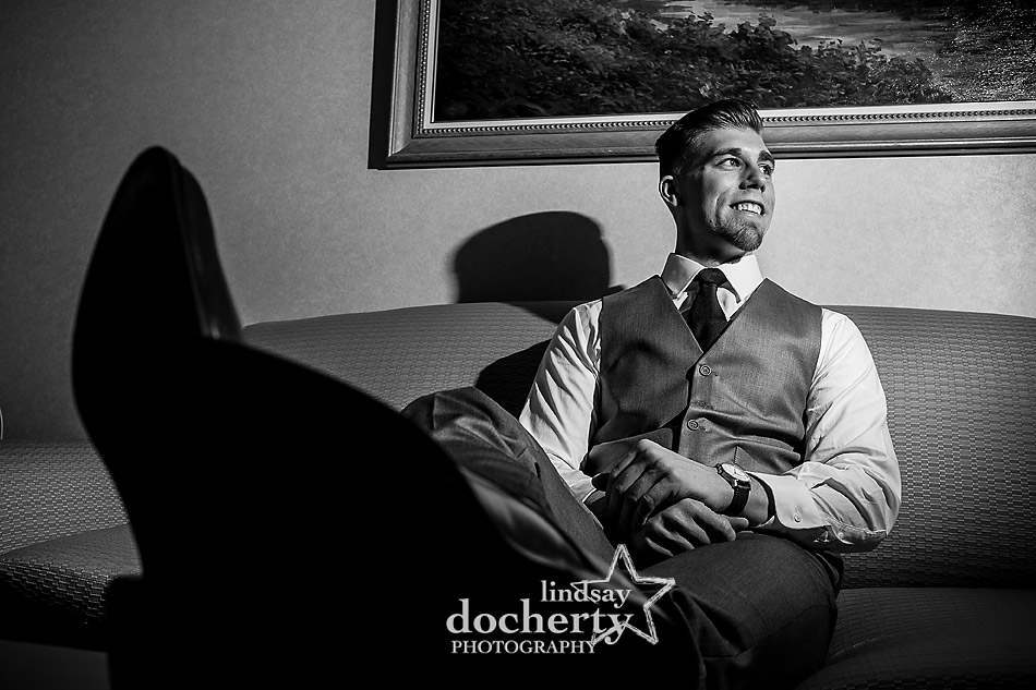 groom portrait on sofa before wedding ceremony