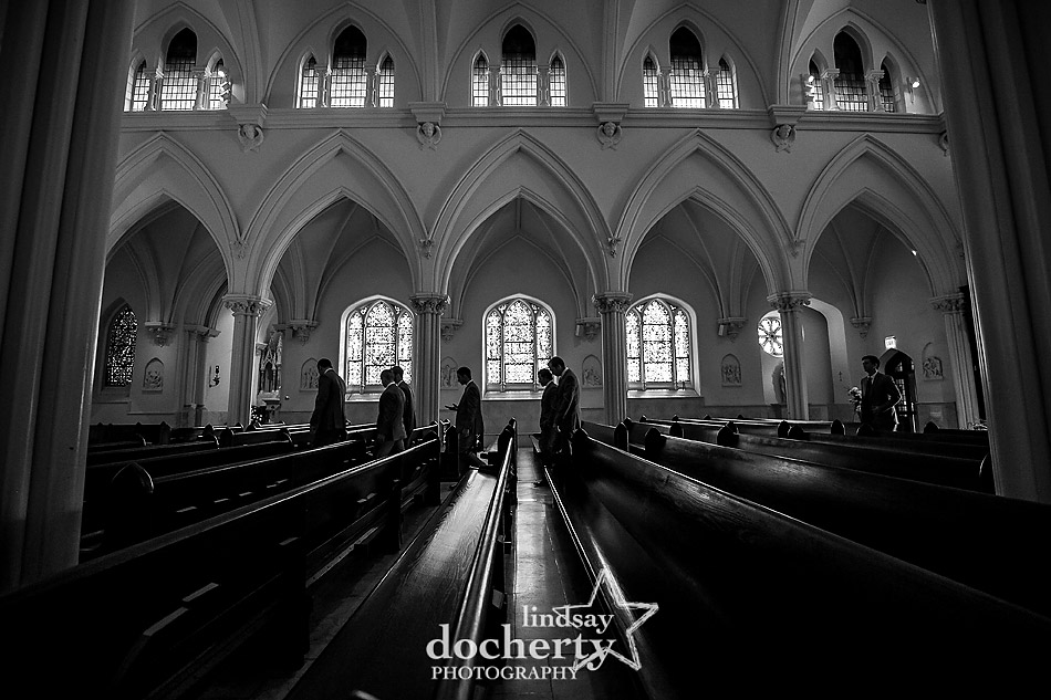 groomsmen walking through church before wedding at St Thomas of Villanova Church
