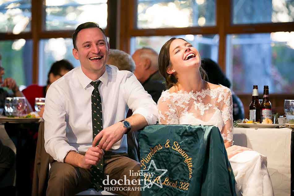 laughing-bride-at-groom-during-speeches-camp-ockanickon-wedding-in-new-jersey