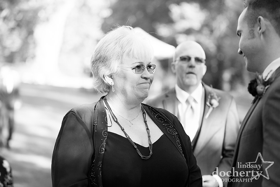 mother handing off son at wedding ceremony