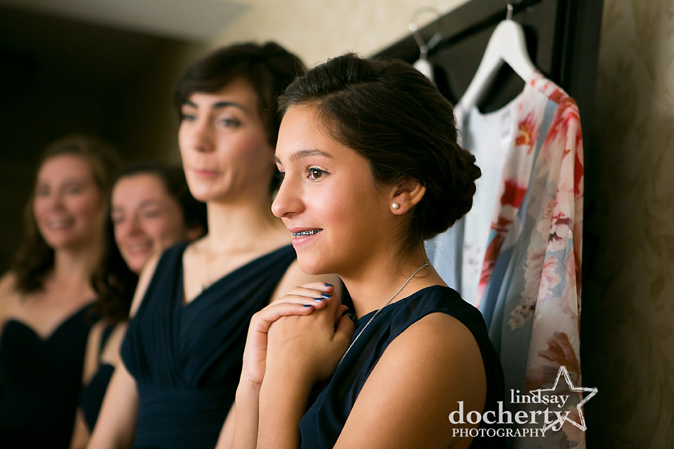 sister and bridesmaids watch bride get ready in wedding dress at Wayne Hotel