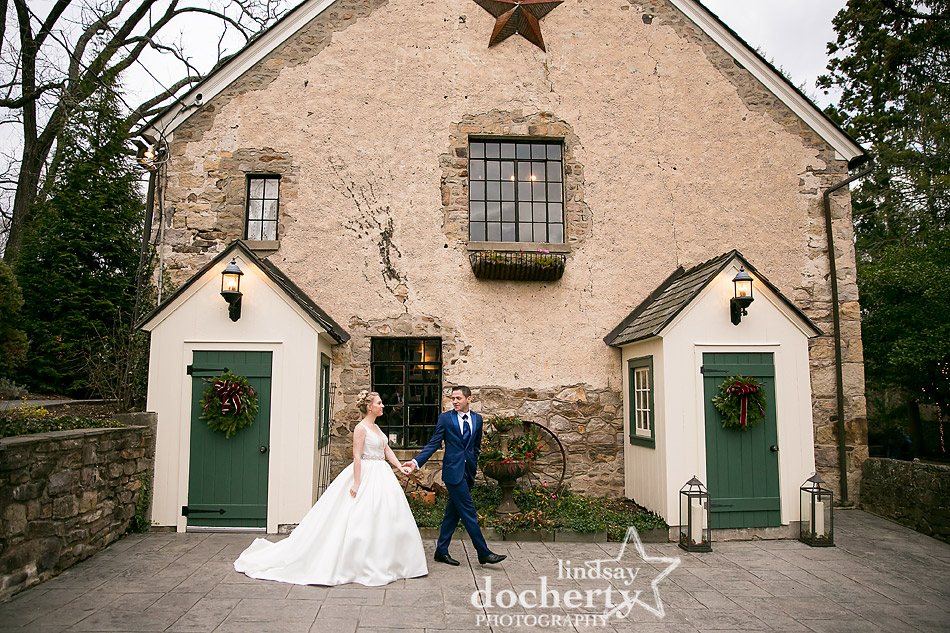 bride and groom walking outside Old Barn at winter wedding at Holly Hedge Estate in New Hope