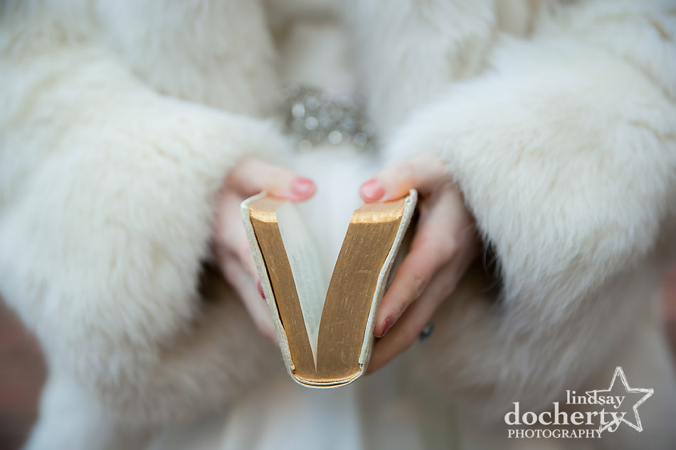 bride holding heirloom bible in fur coat at winter wedding at Holly Hedge Estate