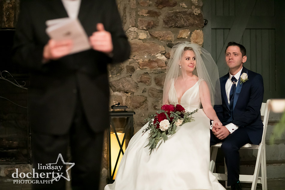 bride looking at groom during indoor ceremony at winter wedding at Holly Hedge Estate in New Hope