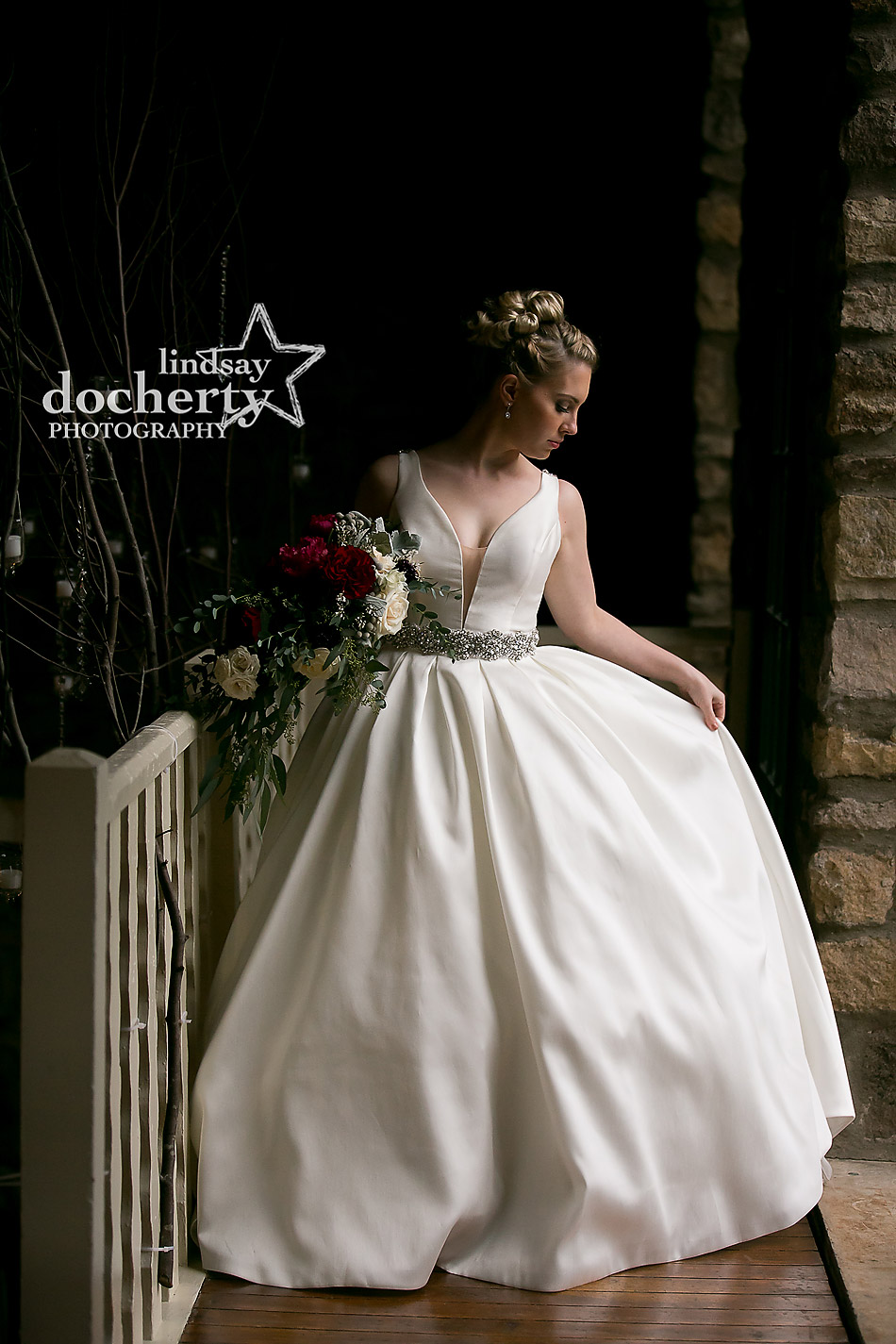bride with deep red flowers and ballgown dress at winter wedding at Holly Hedge Estate in New Hope