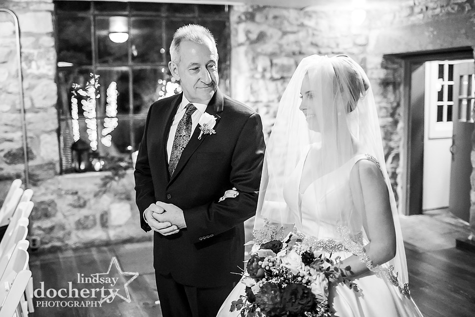 father looking at daughter at end of aisle at winter wedding at Holly Hedge Estate in New Hope