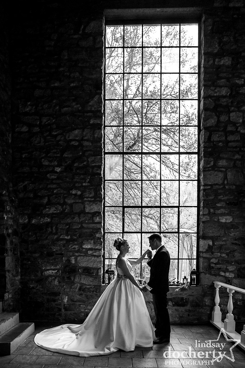 groom kissing brides hand inside Old Barn at winter wedding at Holly Hedge Estate in New Hope