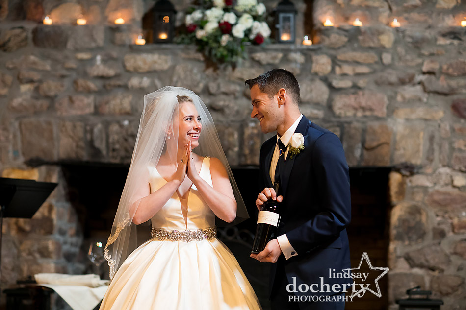 groom sommelier presents bride with wine at winter wedding at Holly Hedge Estate in New Hope