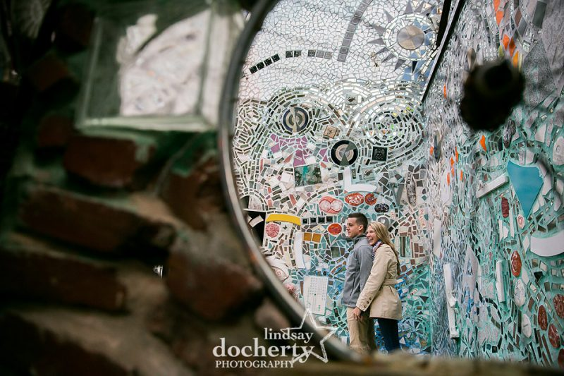 laughing couple proposal and enaggement session in Philadelphia Magic Gardens