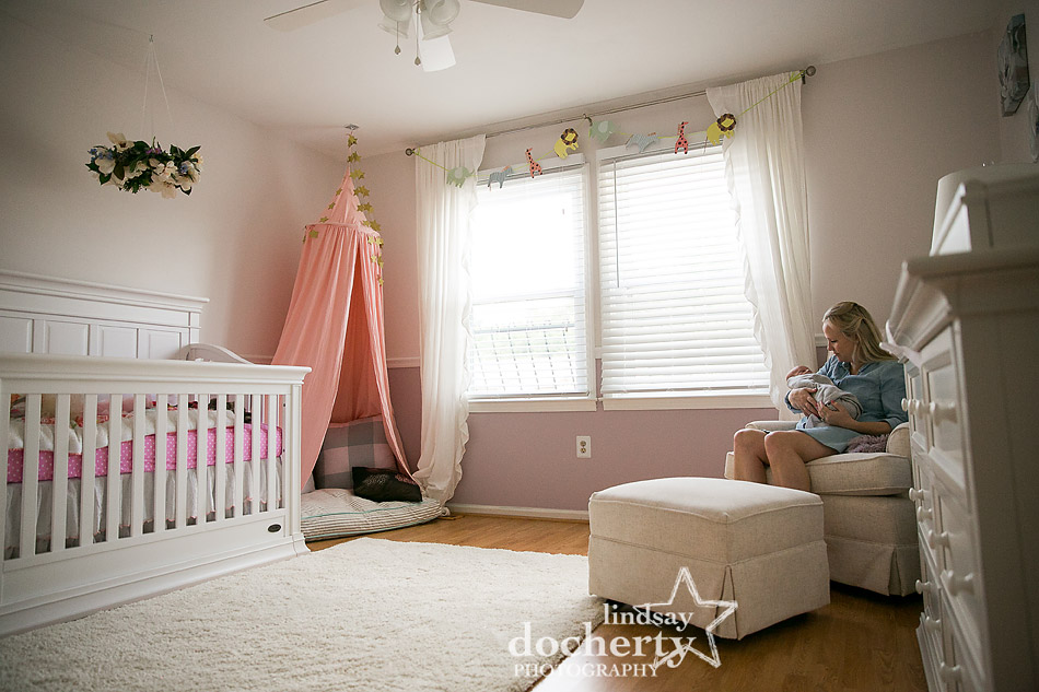 mother and newborn baby girl in pink nursery with pink teepee