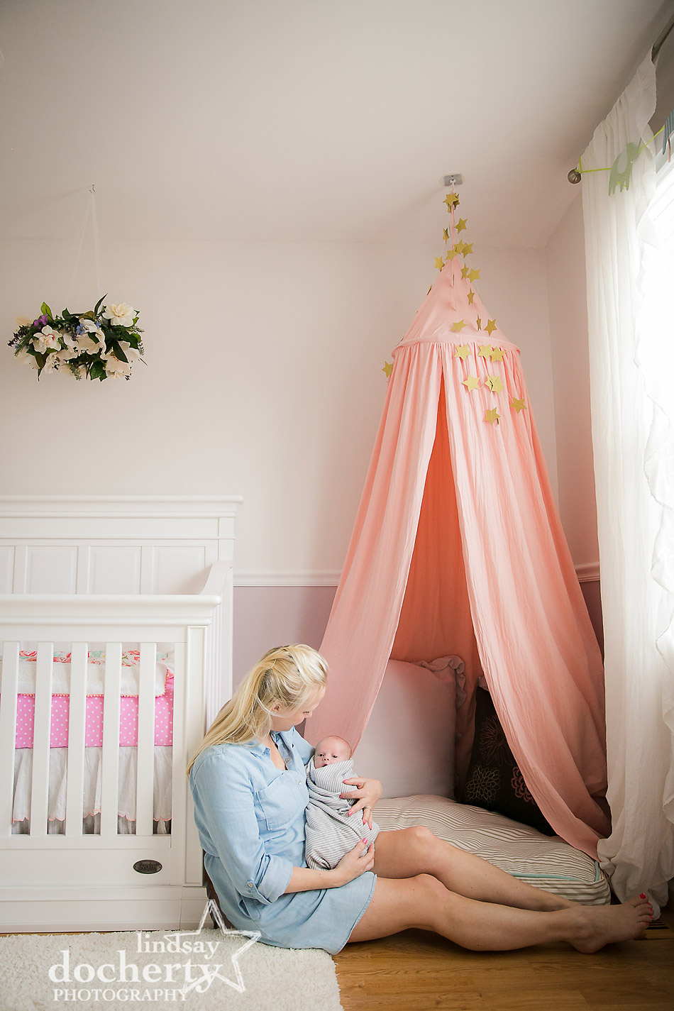 mother in chambray dress at newborn photography session in pink nursery