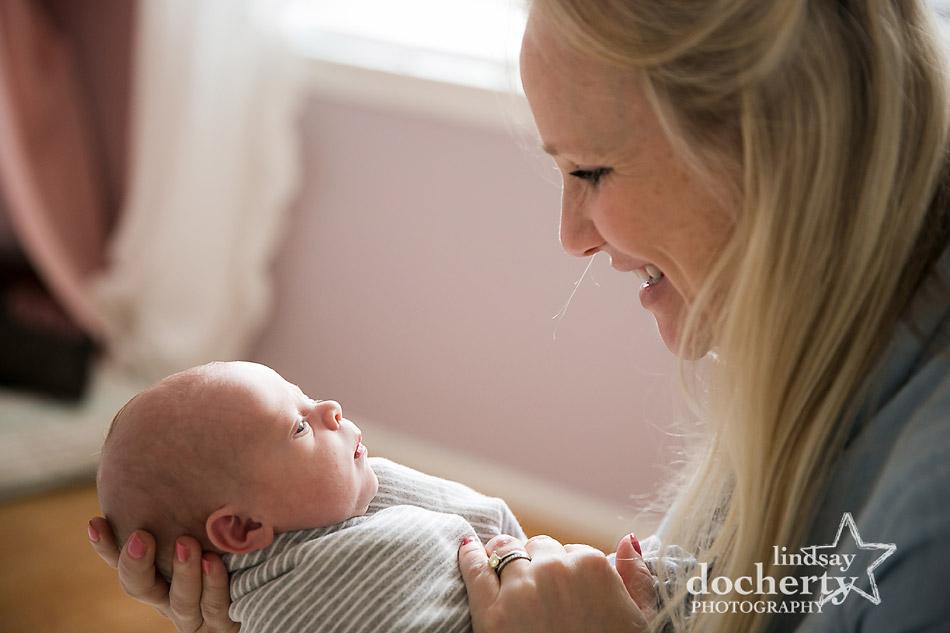 new mom looks lovingly on baby girl in pink nursery