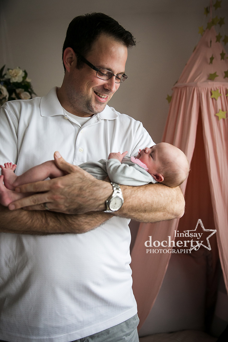 proud father of infant baby girl at newborn photo session