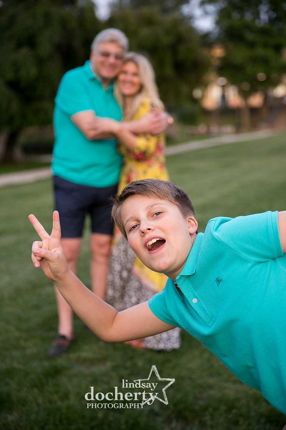 tween boy photobombing photo session with mom and grandfather