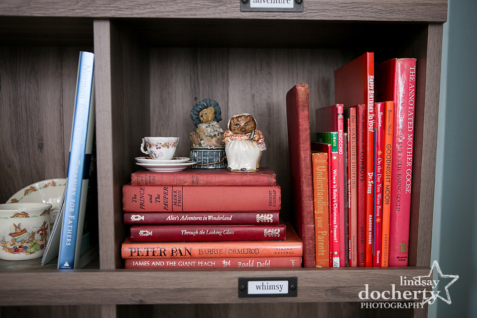 Beatrix Potter and red books on nursery bookshelf