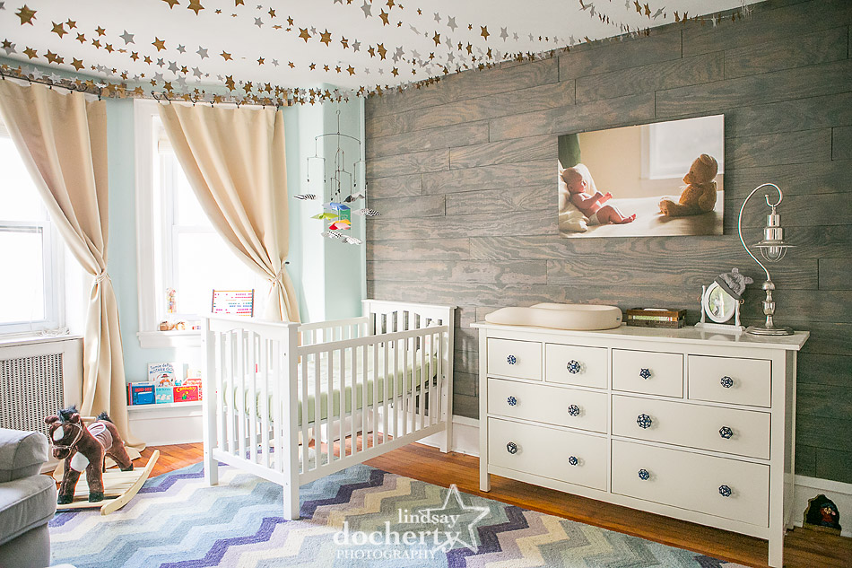 gender neutral light blue nursery with plank accent wall and canvas print