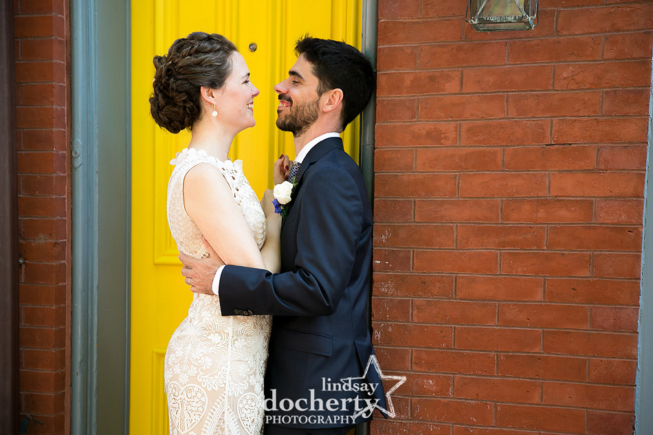bride and groom in front of bright yellow door in Rittenhouse SQuare
