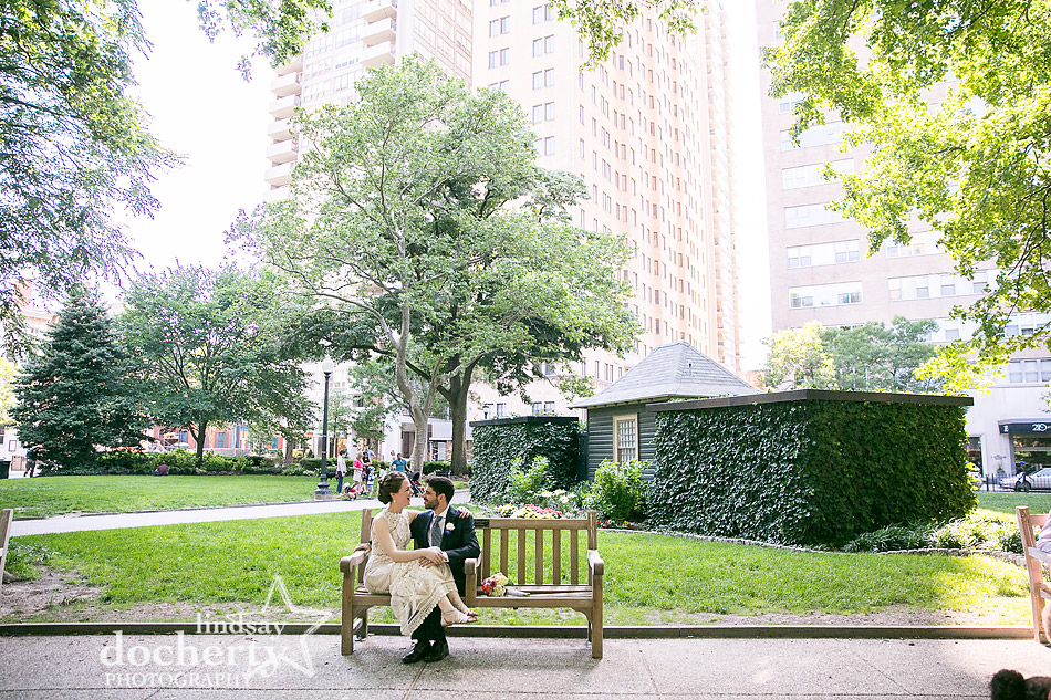 bride and groom sitting on a bench in Rittenhouse Square Philadelphia