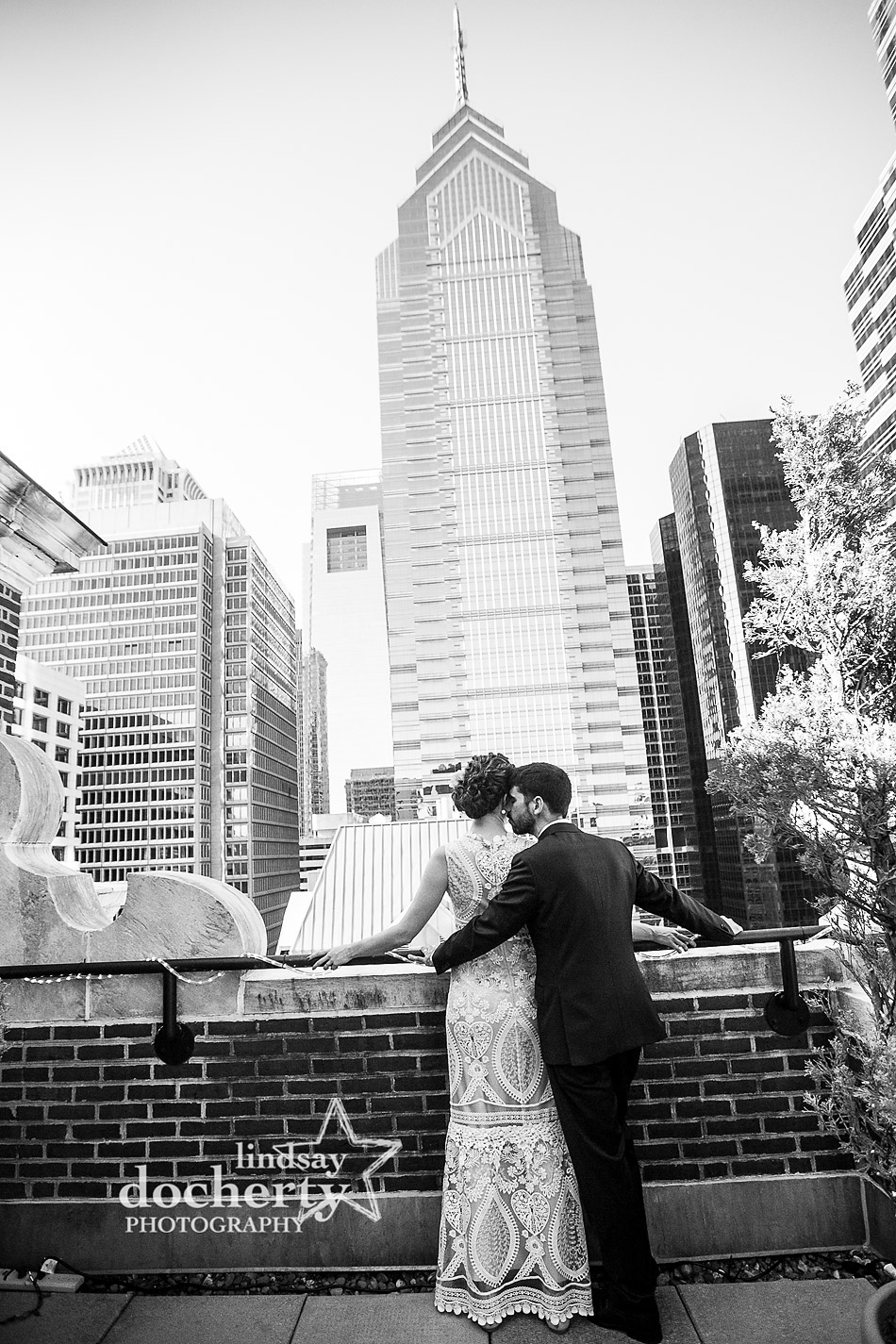 groom kissing wife on Davios roofdeck in Philadelphia