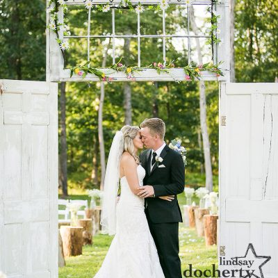 bride and groom kiss under outside wedding doors