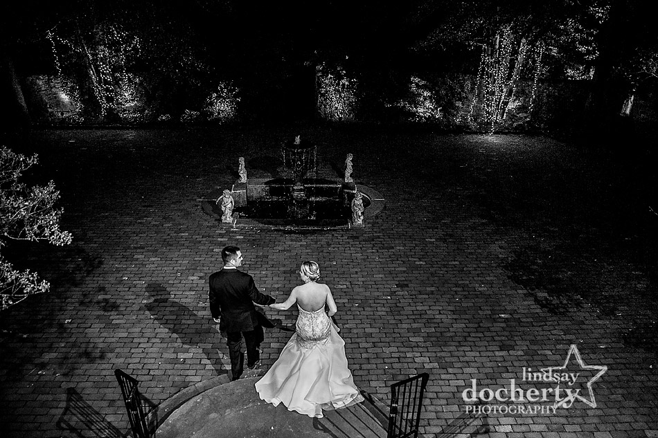 bride and groom walking out onto brick courtyard at night at Holly Hedge Estate