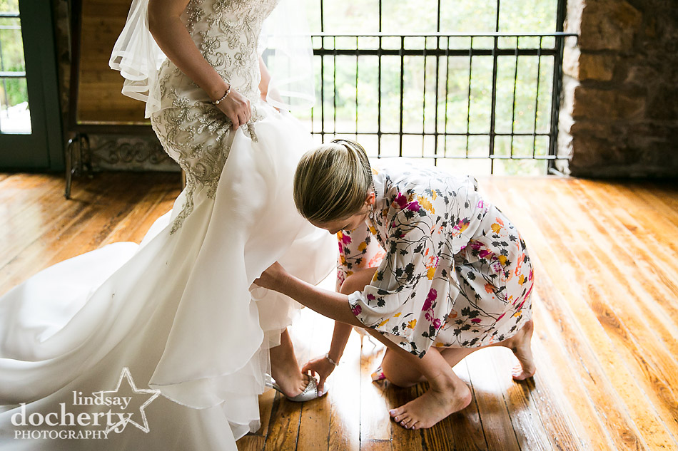 bridesmaid helping bride with shoes