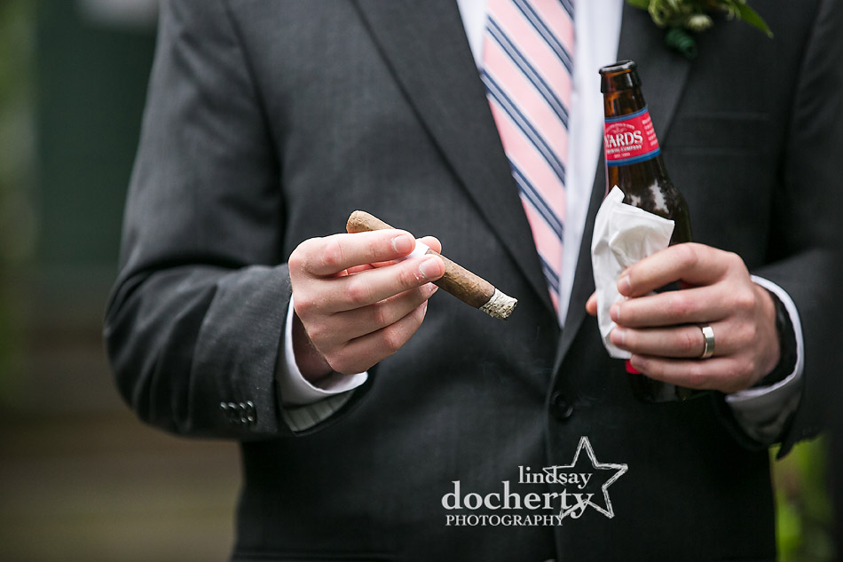 groom with hand rolled cigar at wedding cocktail hour
