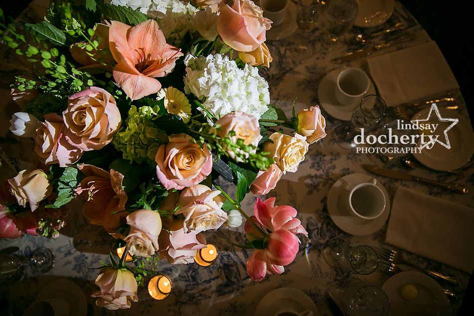 peach and white wedding centerpieces on blue toile tablecloths