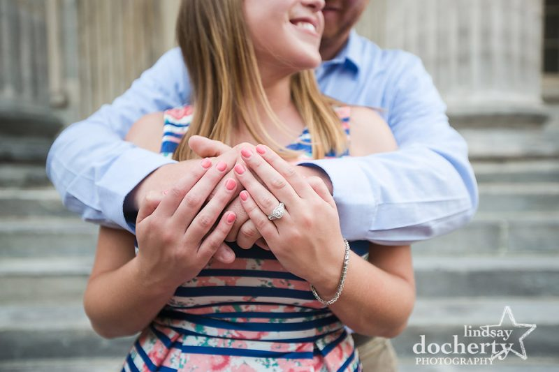 big beautiful diamond engagement ring with groom hugging bride at engagement session in Philadelphia