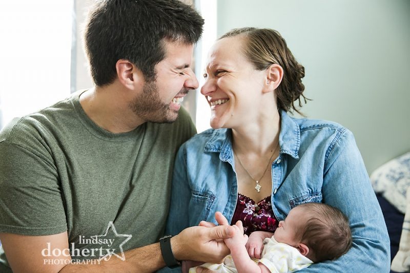 laughing new parents with newborn baby girl