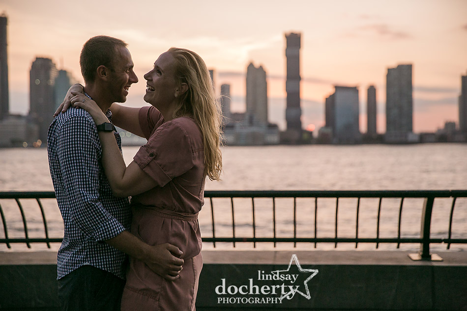 couples laughing as sunsets against skyline in Rockefeller Park