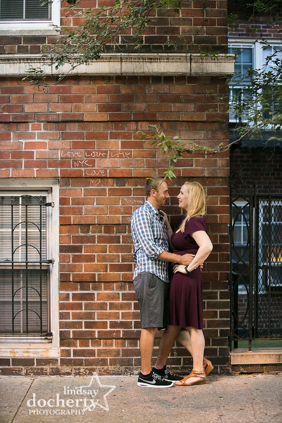 love in chalk on brick wall during an NYC engagement session