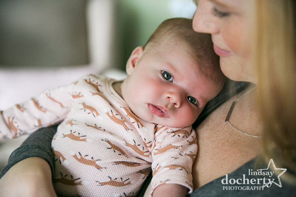 awake baby girl on mommys chest during newborn photo session