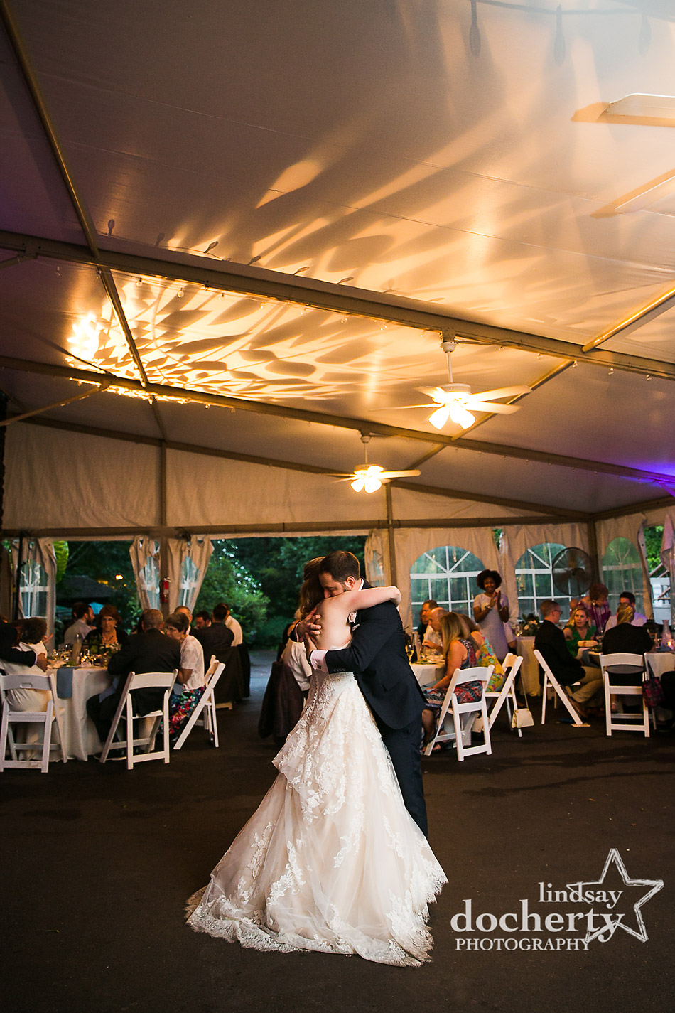 bride and groom hugging at end of first dance under tent at Morris Arboretum