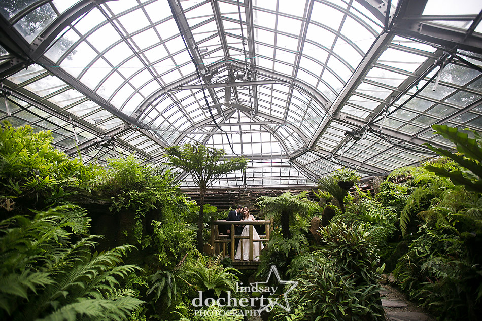 bride and groom in greenhouse fernery at Morris Arboretum on wedding day