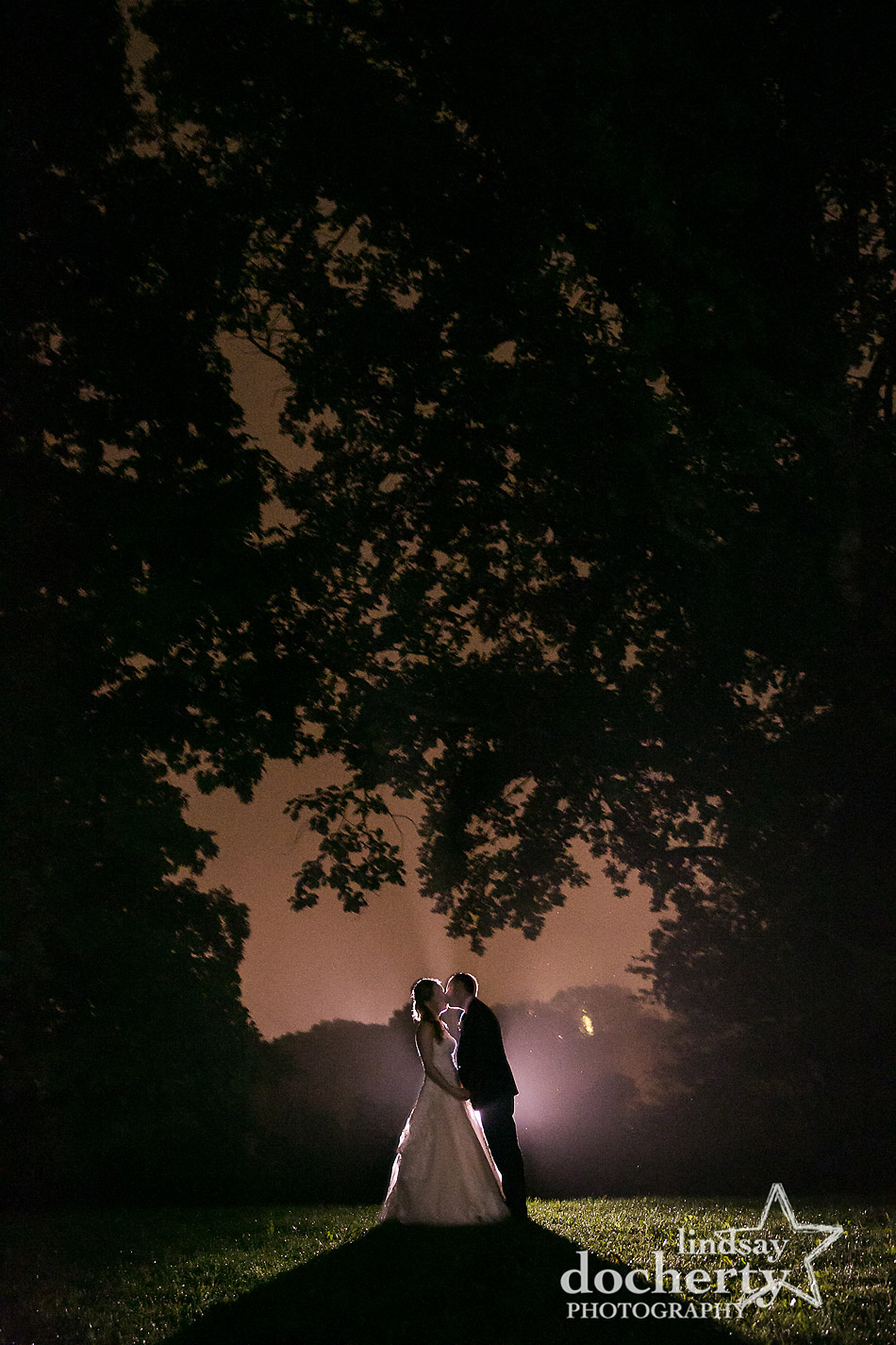 bride and groom kissing in silhouette at night outside at Morris Arboretum