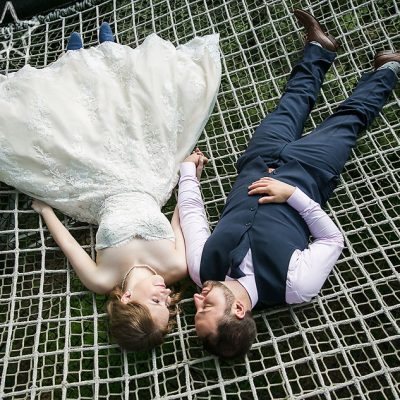 bride and groom lying on netting at Out on a Limb at Morris Arboretum